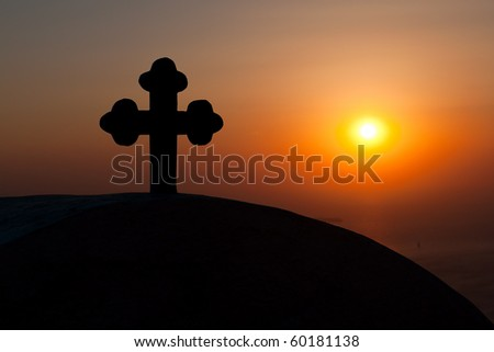Cross on the roof of a church during sunset in Santorini island