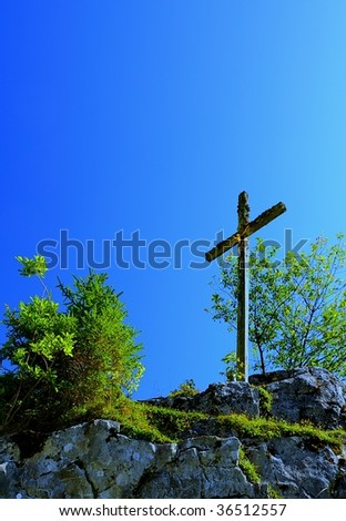 Cross on the summit of a mountain in the alps - stock photo
