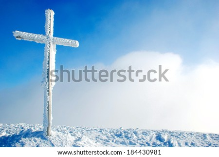 Cross on the top of the mountain in winter - stock photo