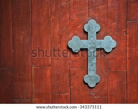 Cross on wooden door - stock photo