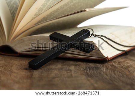 Cross over wood table with old book, holy Bible - stock photo