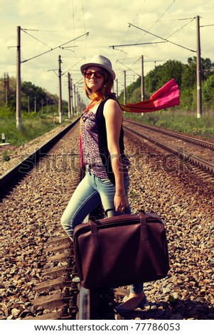 cross process technique reproduction showing beautiful young girl walking on railroad tracks with suitcase and  hat in casual - stock photo