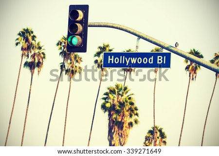 Cross processed Hollywood boulevard sign and traffic lights with palm trees in the background, Los Angeles, USA. - stock photo