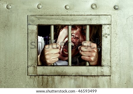 Cross-processed image of a man going insane, grabbing the bars of his jail cell, looking rabid and screaming uncontrollably - stock photo