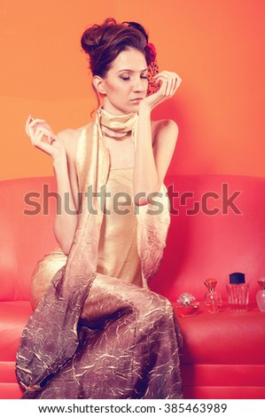 Cross processed image of beautiful elegant lady trying out perfumes while sitting on couch.