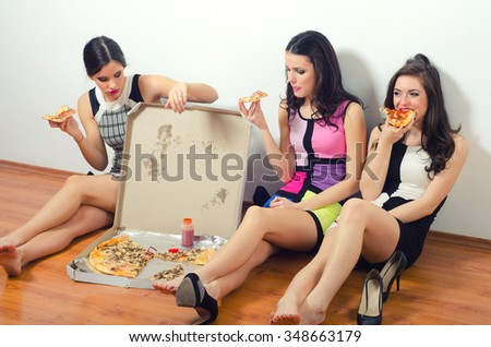 Cross processed image of three beautiful young ladies eating pizza while sitting on the floor. - stock photo
