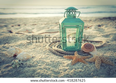 Cross-processed lantern on the beach with shells and rope at sunrise - stock photo