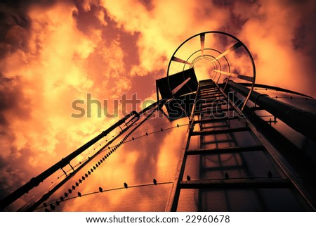 Cross processed low-angle shot of ladder on tank refinery. - stock photo