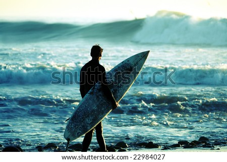Cross-processed of a surfer at dusk - stock photo