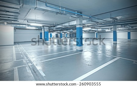 Cross processed photo of underground parking, industrial interior background. - stock photo