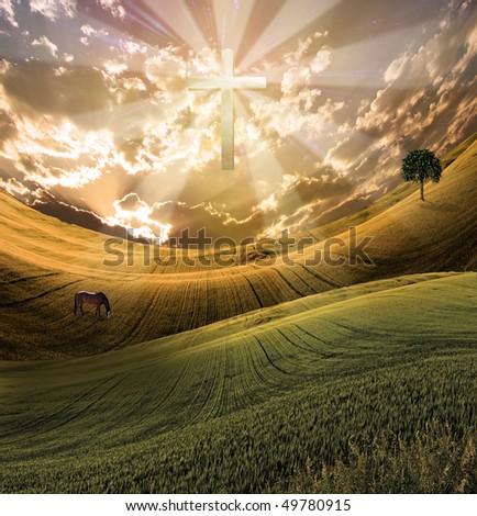 Cross radiates light in sky over beautiful landscape - stock photo