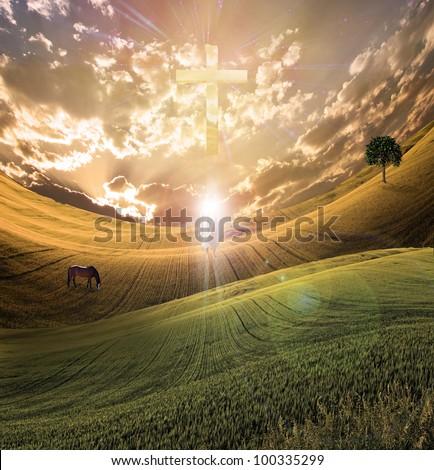 Cross radiates light in sky over beautiful landscape along with figure of light - stock photo