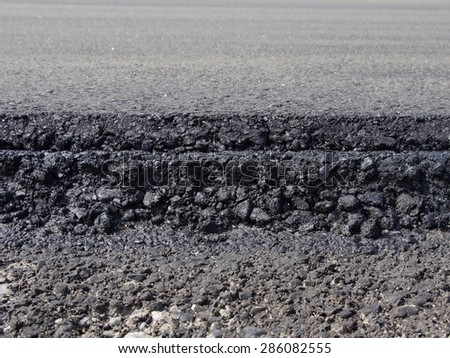 Cross-section of a freshly overlayed paved asphalt roadway- road construction - stock photo