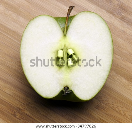 Cross section of apple with pills in place of seeds