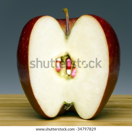 Cross section of apple with pills in place of seeds - stock photo