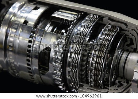 Cross section of automatic gearbox isolated on black - stock photo