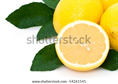 Cross section of ripe lemons and whole lemons with green leaves on white background