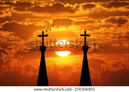 Cross silhouette of steeple lamp with sunset background - stock photo