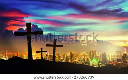 cross silhouette on mountain with twilight sky and cityscape on background. - stock photo