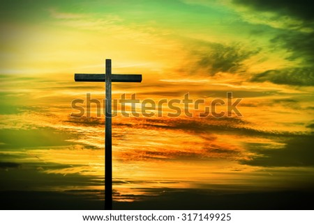Cross silhouette over green and yellow dramatic sky at sunset - stock photo