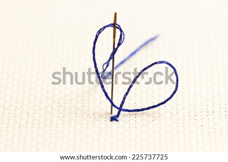 cross-stitch embroidery on a canvas with a needle with blue thread close-up