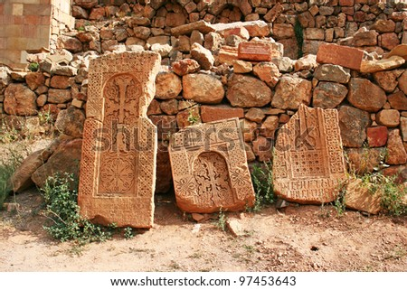 Cross-stones at Noravank monastery in Armenia, red rocky mountains.