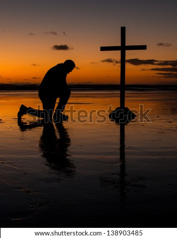Cross with a man kneel in prayer on a beach at sunset. - stock photo