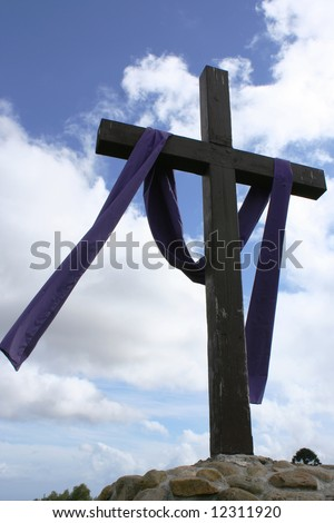 Cross with blue sky and clouds in background.  The cross is located at the Santa Barbara Mission, California. - stock photo