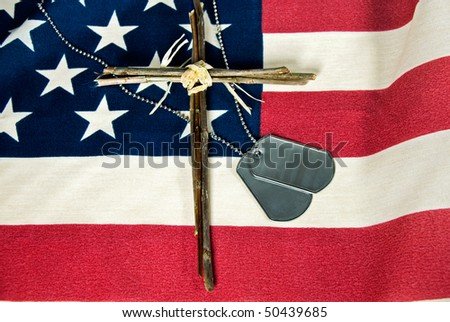 cross with military dog tags on flag