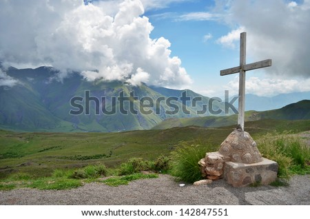 Cross with mountains and cloudy sky on the background - stock photo