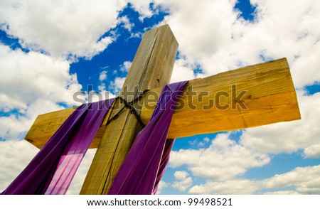 Cross with purple drape or sash for Easter with blue sky and clouds in background - stock photo