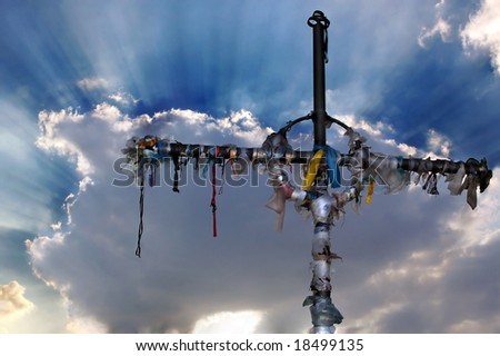 Cross with ribbons against clouds - stock photo