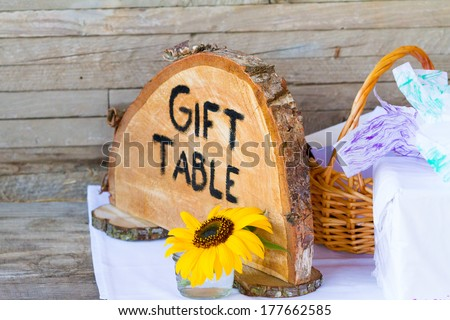Crosscut section of a tree says gift table to label things with a sign at the wedding ceremony of a bride and groom. - stock photo