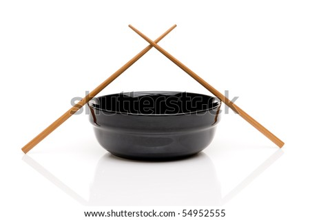 Crossed chopsticks on a black bowl on white - stock photo