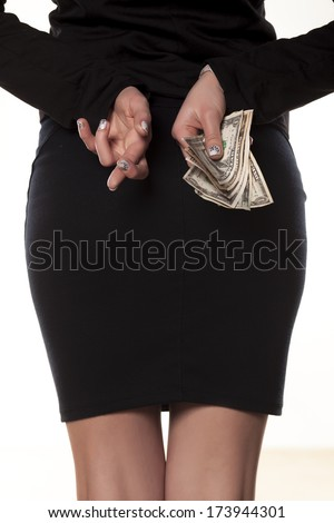 Crossed fingers and keep the money behind her back - stock photo