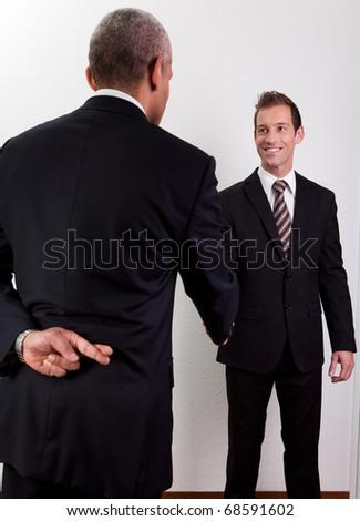 Crossed Fingers At Handshake - stock photo