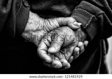 Crossed Hands in black and white of old retired man who had worked hard in his life as farmer - stock photo