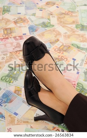 Crossed legs on banknotes (money under control and security concepts) - stock photo