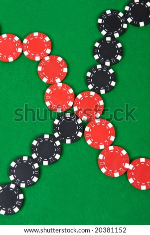 Crossed lines of red and black poker chips on green poker table. Top view.