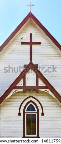 Crosses and window on the front of a wooden rural church