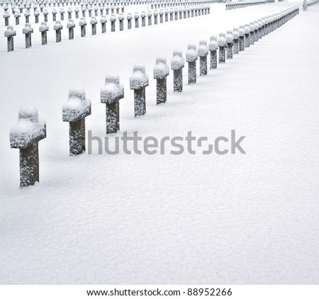 crosses at WW2 military graveyard covered in snow ice cold cemetery - stock photo