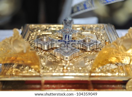 crosses , rings and crowns of gold on the table in church.Wedding celebration - stock photo