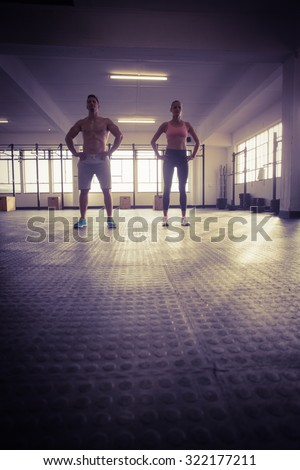 Crossfit couple facing camera with hands on hips in crossfit gym - stock photo