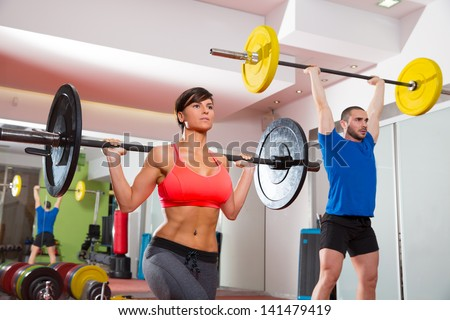 Crossfit fitness gym weight lifting bar by woman and man group workout - stock photo
