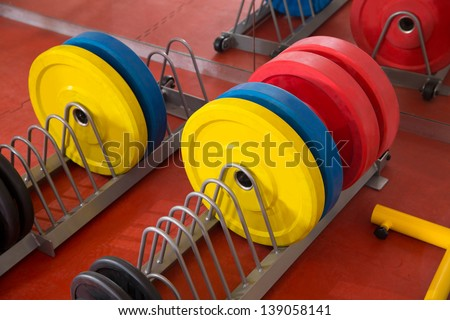 Crossfit fitness gym weight lifting bar colorful equipment on red floor - stock photo