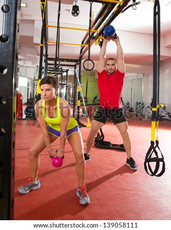 Crossfit fitness Kettlebells swing exercise man and woman workout at gym - stock photo