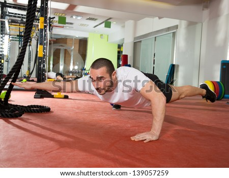 Crossfit fitness man balance push ups with one leg and arm up exercise at gym workout - stock photo