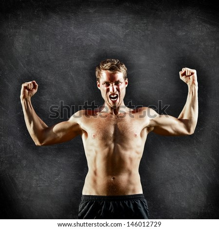 Crossfit fitness man flexing strong and aggressive showing muscles on blackboard background with copy space for text. Male cross fitness trainer on chalkboard background showing biceps muscles - stock photo