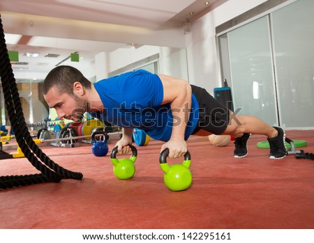 Crossfit fitness man push ups Kettlebells pushup exercise at gym workout - stock photo
