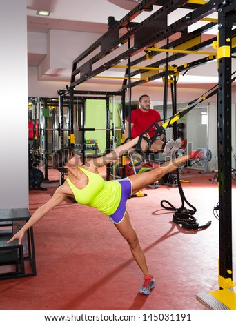 Crossfit fitness TRX training exercises at gym woman and dip rings man workout - stock photo